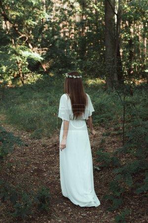 back view of girl in white elegant dress walking in forest