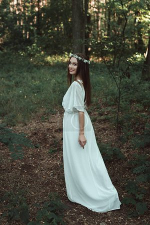 attractive smiling girl in white dress walking in forest