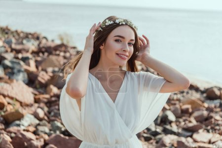 happy girl posing in white dress and wreath on rocky beach