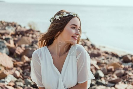 attractive smiling girl posing in floral wreath on rocky beach near sea
