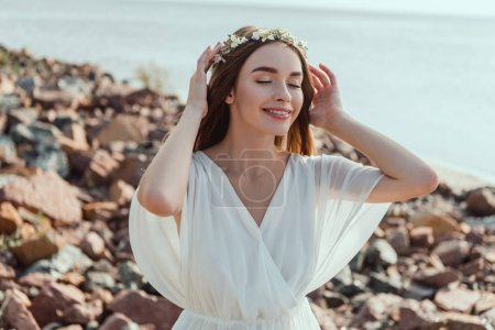 beautiful smiling girl posing in white dress and floral wreath on rocky beach