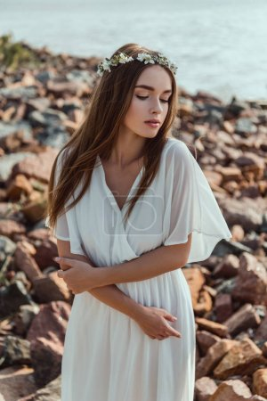 beautiful young tender woman posing in floral wreath on rocky beach