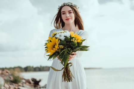 beautiful elegant girl holding bouquet with yellow sunflowers
