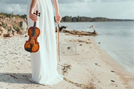cropped view of elegant girl in white dress holding violin on sand beach