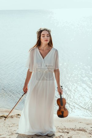 attractive woman with closed eyes posing in elegant dress and holding violin near sea