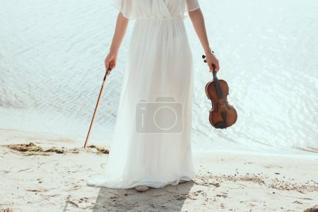 cropped view of girl in white dress holding violin on seashore
