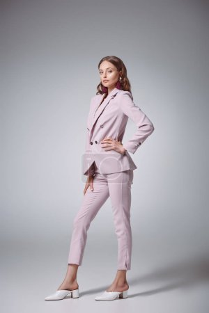 full length view of beautiful woman in stylish pink suit posing with hand on waist and looking at camera on grey