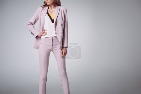 cropped shot of confident woman in fashionable suit posing with hand on waist isolated on grey