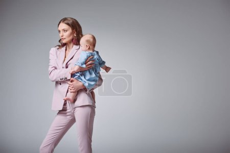 beautiful stylish young mother carrying adorable infant daughter and looking away isolated on grey
