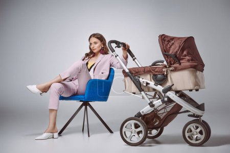 stylish woman holding baby stroller while sitting on chair and looking away on grey