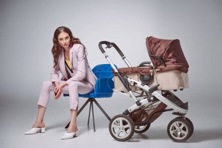 beautiful woman in fashionable suit sitting on chair near baby carriage and looking at camera on grey