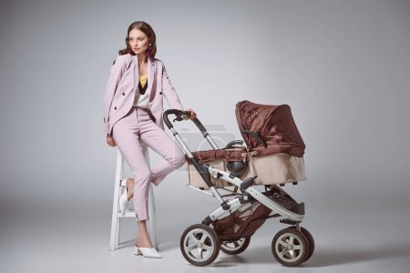 fashionable young woman with baby carriage sitting on stool and looking away on grey