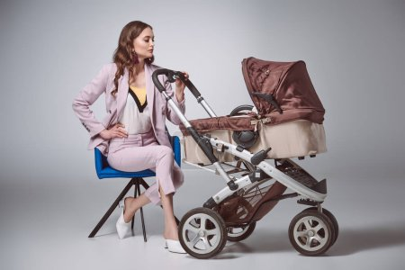 beautiful stylish young woman sitting on chair and looking at baby carriage on grey