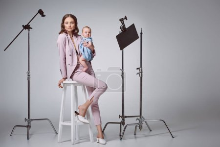 beautiful stylish mother holding adorable infant daughter and looking at camera while sitting on stool in recording studio