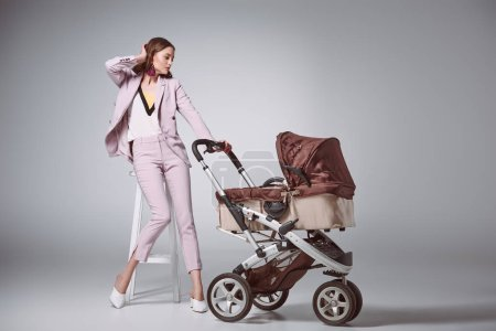 beautiful woman in stylish suit sitting on stool and looking at baby carriage on grey