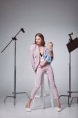 stylish young mother carrying adorable infant daughter while sitting on stool in recording studio
