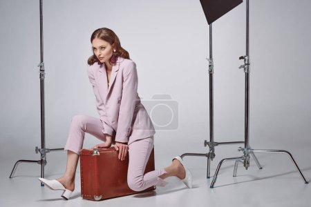 beautiful stylish woman in pink suit sitting on suitcase and looking away in recording studio