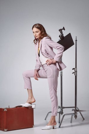 beautiful fashionable woman posing with suitcase and looking away in recording studio
