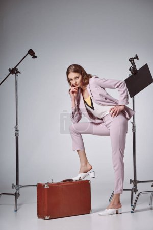 beautiful fashionable woman posing with suitcase and looking at camera in recording studio