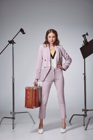 beautiful fashionable woman with suitcase posing with hand on waist and looking at camera in recording studio