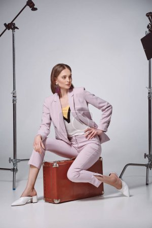 fashionable woman in pink suit sitting on suitcase and looking away in recording studio
