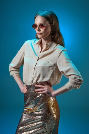 beautiful woman in fashionable golden glittering skirt and sunglasses posing with hands on waist isolated on blue