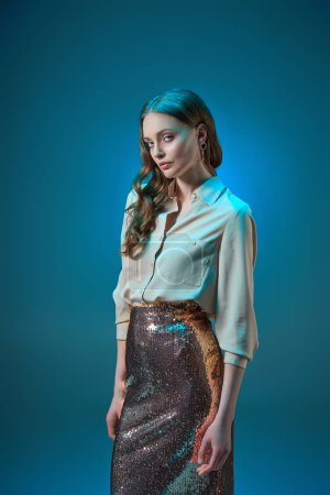 beautiful woman in fashionable golden glittering skirt looking at camera isolated on blue