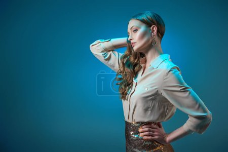beautiful woman in fashionable golden glittering skirt posing with hand on waist and looking away isolated on blue