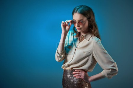 beautiful stylish woman adjusting sunglasses and posing with hand on waist isolated on blue