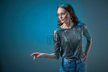 Photo pour À la mode jeune à lunettes posant avec la main sur la taille et à la recherche isolées loin sur bleu - image libre de droit