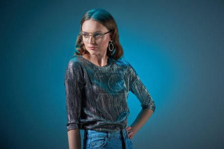 beautiful woman in stylish outfit and eyeglasses posing with hand on waist and looking away isolated on blue