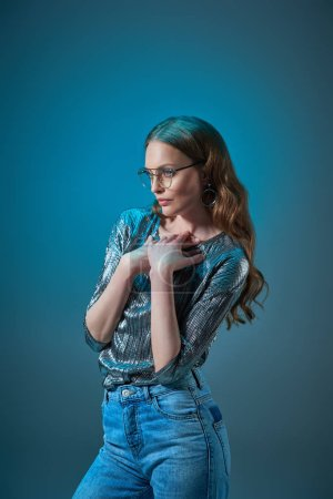 beautiful woman in stylish outfit and eyeglasses looking away isolated on blue