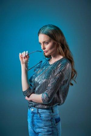 Photo pour La mode femme tenant des lunettes de vue et à la recherche de loin bleu isolé sur - image libre de droit