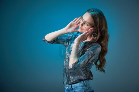 beautiful stylish woman wearing spectacles and looking away isolated on blue