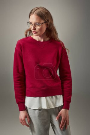 portrait of beautiful woman in stylish red sweater and spectacles looking away isolated on grey