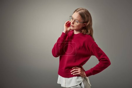 beautiful woman in stylish red sweater and eyeglasses looking away isolated on grey