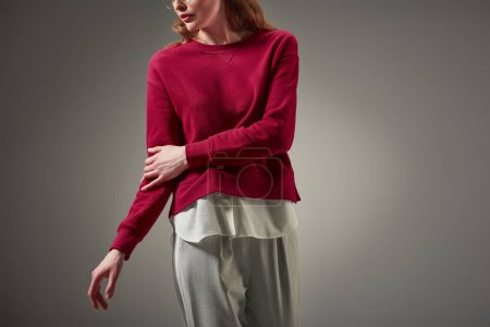cropped shot of woman in red sweater and stylish pants posing isolated on grey