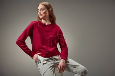 beautiful woman in red sweater sitting on stool and looking away isolated on grey