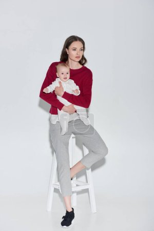 full length view of beautiful stylish woman holding adorable baby girl and sitting stool on grey