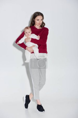 full length view of beautiful young mother in stylish outfit carrying adorable baby girl on grey