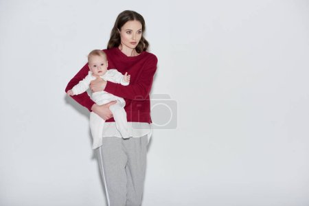 beautiful stylish young mother carrying adorable baby girl and looking away on grey