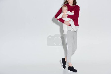 cropped shot of stylish mother carrying adorable baby girl on grey