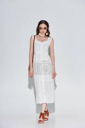Photo pour Vue de la pleine longueur de jolie femme élégante en robe blanche et lunettes de soleil caméra en regardant sur fond gris - image libre de droit