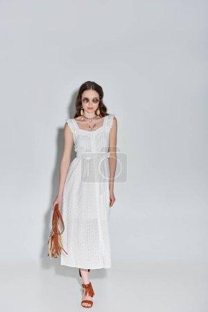 Photo pour Vue de la pleine longueur de belle femme en robe blanche élégante et lunettes de soleil tenant le sac à main et marche sur fond gris - image libre de droit