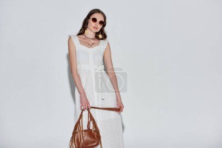 beautiful woman in stylish white dress and sunglasses holding handbag and looking at camera on grey