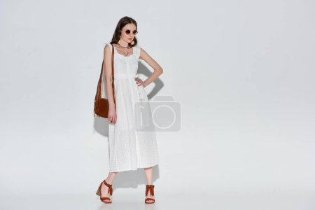 beautiful woman in stylish white dress and sunglasses posing with hand on waist on grey