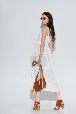 side view of beautiful woman in stylish white dress and sunglasses holding handbag on grey