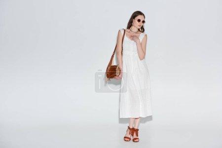 beautiful woman in stylish white dress and sunglasses posing on grey