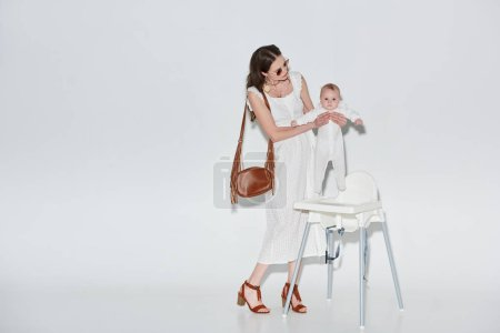 stylish woman in white dress and sunglasses carrying baby girl near high chair on grey