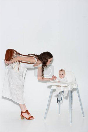beautiful stylish woman looking at adorable infant daughter sitting in high chair on grey